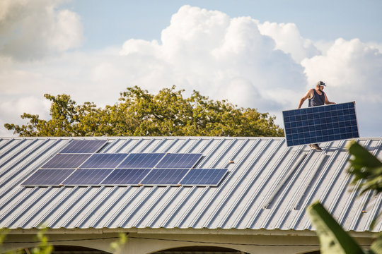 Man carrying solar panel on rooftop.