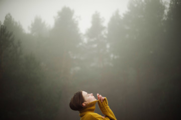 Thoughtful woman standing by forest in foggy weather