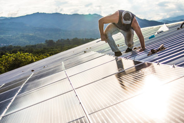 Worker carefully works to secure solar panels on roof of building.