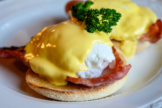 Weekend brunch in Scotland with two eggs benedict on homemade muffuns with roasted bacon and yellow hollandaise sauce.