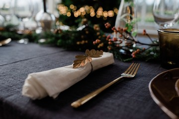 gold napkin holder on a decorated dinner table with candles