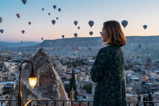 Woman soaking in a magical hot air balloon morning in Cappadocia