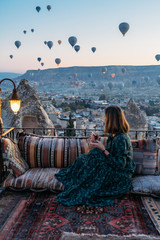 Woman drinking early morning tea with hot air balloons in Cappadocia