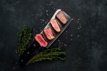 Four steaks on knife on a stone background. Four types of meat frying Rare, Medium, Medium Good, Well done Wall mural