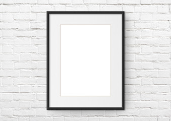 Empty frame. Blank black mounted portrait frame on white brick wall