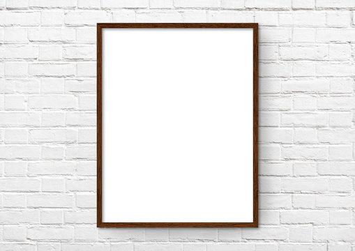 Empty frame. Blank dark wood mounted portrait frame on white brick wall