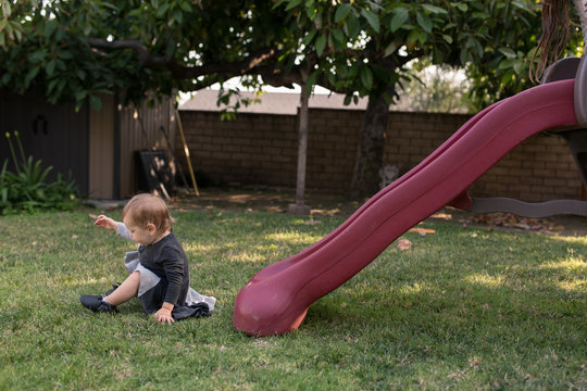 Two girls are helping their toddler baby sister go down a slide in their backyard during summertime in California.