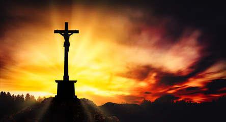 Cross with Christ on the top of the rocky mountain at sunset