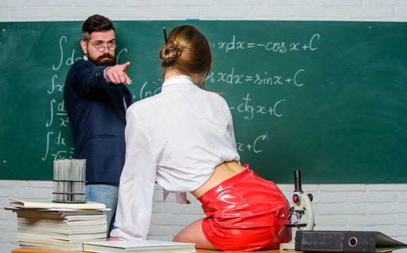 She is a seduction guru. Bearded man point finger at sexy woman. Sensual teacher use sexy seduction tactics. Seduction and temptation in school. Sexi girl in mini skirt, rear view