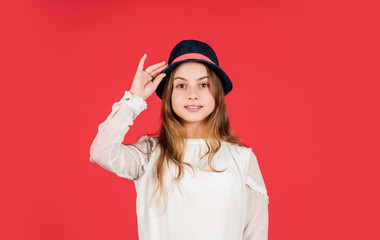 Feeling fancy. Child long hair wear hat. Accessories shop. Outfit inspiration. Individual style. Girl wear hat red background. Happy kid in hat. Fashion accessory. Summer accessory collection