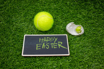 Fototapeta Tennis Easter with tennis ball and happy Easter sign with chicken on green grass obraz