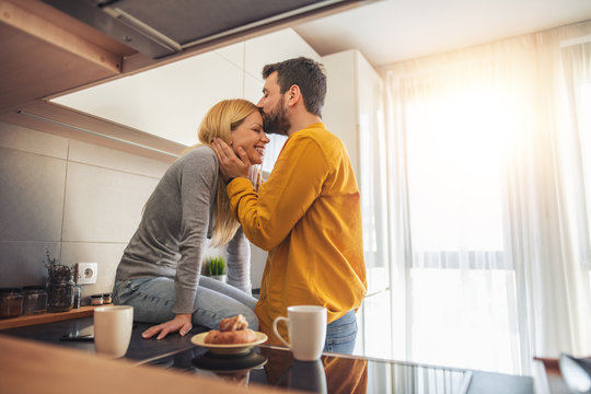 Young couple relaxing at home with cup of coffee