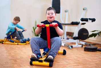 happy young kid with down syndrome exercising on inclusive sport equipment, developing muscular strength at rehabilitation center