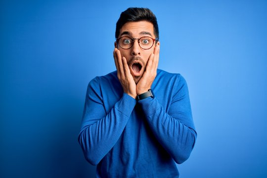 Young handsome man with beard wearing casual sweater and glasses over blue background afraid and shocked, surprise and amazed expression with hands on face