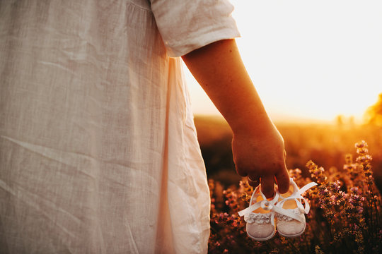 Caucasian woman dressed in a white dress is posing in a wheat field while holding a pair of baby shoes