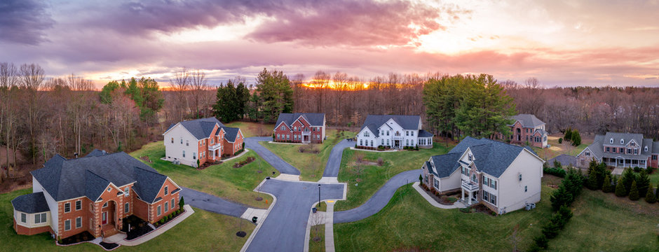 Aerial sunset panorama of brick facade luxury mansion type single family homes neighborhood cul-de-sac street American real estate in a new construction in Maryland USA with dramatic sky