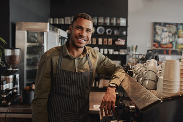 Portrait of young afro-american male business owner behind the counter of a coffee shop smiling looking at camera Fotobehang