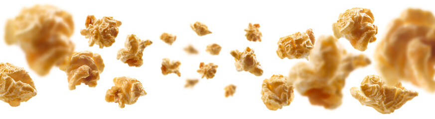 Caramel-flavored popcorn levitates on a white background