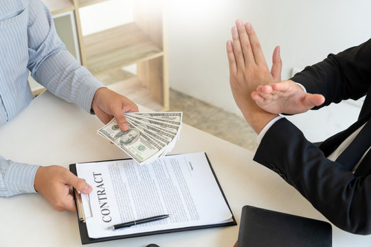 Businessman rejecting money or refusing money form of dollar bills to take the bribe to agreement contract, anti bribery and corruption concept.