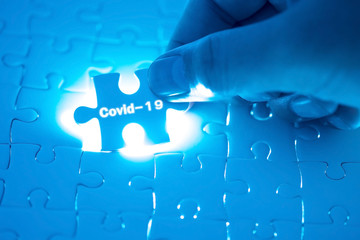 Doctor's hand holding a jigsaw puzzle with Covid-19 words. Health concept. Stop Novel Coronavirus outbreak covid-19 2019-nCoV symptoms in the world.