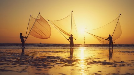 Tan Thanh beach, Go Cong district, Tien Giang province, Vietnam - Feb 2020: Photo of fishing village people using homemade tools to catch fish in sea at sunrise