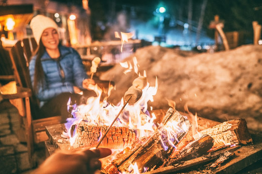 Winter holiday ski resort woman roasting marshmallows in BBQ firepit afterski fun leisure activity with friends. Couple grilling marshmallow stick in fire.