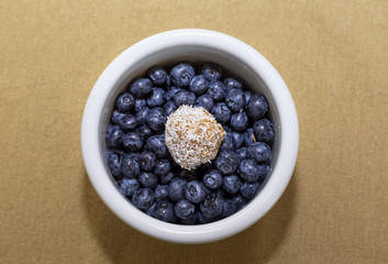 Penaut and dates ball with coconut shrims on blueberries in white bowl