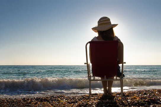 a young girl sitting on a chair watching the sunset at the beach