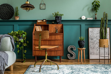 Stylish interior design with retro wooden cabinet, chair, elegant sofa, plants, cube, stool, decoratnion, poster and personal accessories. Modern retro concept of home office space. Template.