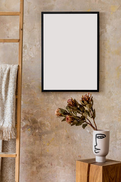Modern composition of living room interior with black mock up poster frame, wooden cube, flowers in vase, ladder and elegant personal accessories. Stylish home decor. Grunge wall. Wabi sabi. Template.