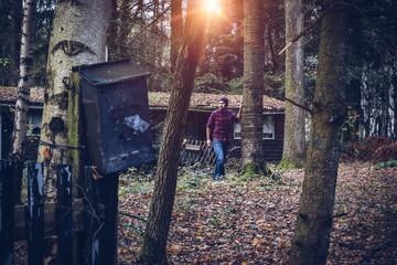 Homme dans un bois avec une cabane Wall mural