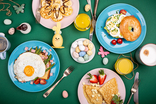 Easter composition with breakfast flat lay with scrambled eggs bagels, tulips, pancakes, bread toast with fried egg and green asparagus, colored quail eggs. Top view.