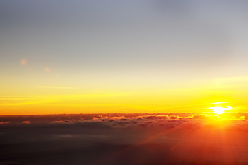 Fotobehang - The sun rising from the clouds and fog. Top view from the mountain to a beautiful foggy distance.