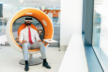 Relaxed businessman enjoying virtual video in modern office lounge. Man in office clothes and virtual reality glasses sitting in interactive chair and turning face up. Relaxing in office concept