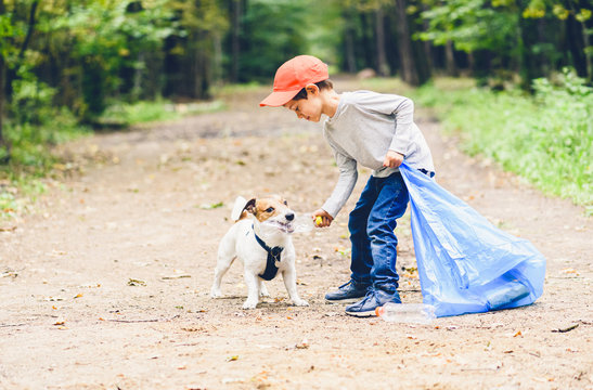 Earth day concept with kid and dog cleaning park gathering plastic bottles