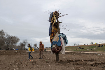 Migrants pass a tree where they left blankets to dry near the Tunca river in Edirne