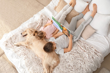 Little children with dog reading book in bedroom at home