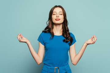 Fototapeta smiling girl standing in meditation pose with closed eyes on blue background obraz