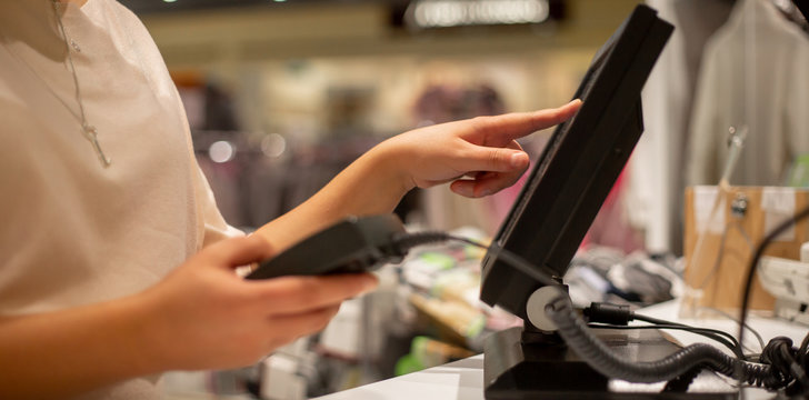 Saleswoman doing process payment on touchscreen pos, counting sale, finance concept