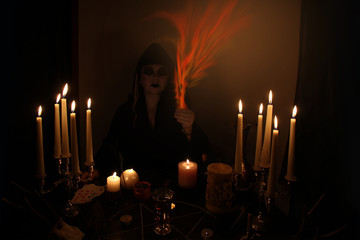 Female Fortuneteller conjures in a dark room, candles are burning on a round esoteric table with a pentagram, animal skulls lie, the concept of magic, witchcraft