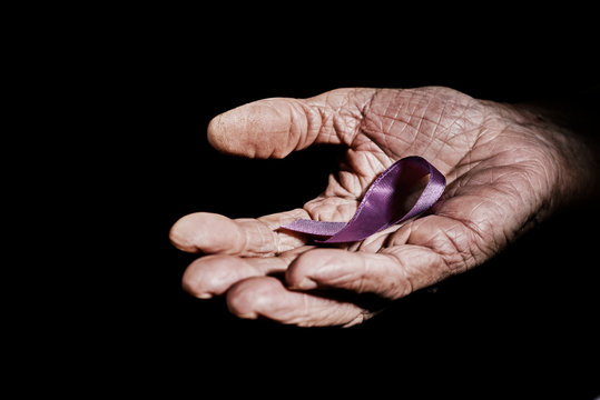 senior woman with a purple ribbon in her hand