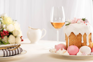 selective focus of delicious Easter cake decorated with meringue with pink and white eggs on plate near wine glass and flowers
