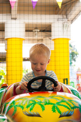 Foto op Aluminium Amusementspark A very joyful and happy little blond boy of three years old is riding in a yellow car with a green car in the summer Riviera Amusement Park