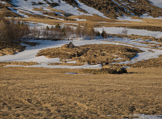 Ein Traktor hinter einer Torfhaus Ruine in Island
