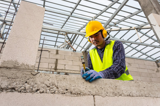 Construction workers use a hammer to hammer a concrete nail into a lightweight concrete block to build a house.