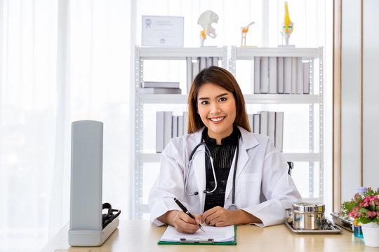 Portrait of a smiling Asian medical doctor sitting at desk in office clinic hospital wearing white coat with stethoscope, looking at camera