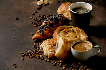 Variety of traditional french puff pastry raisin and chocolate buns, croissant with various cups of coffee paper and ceramic, coffee beans, recycled wooden spoon of sugar over dark texture background. Fototapete