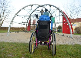 Boy in a wheelchair watching kids on a playground