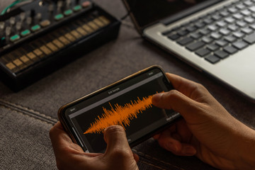 Young man editing audio in a smartphone application with a computer and a background synthesizer Music concept