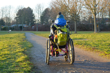 Lonely child in a wheelchair on a muddy path outdoor